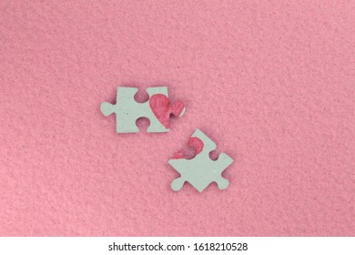 Puzzle with a red heart on the pink felt background. Two disconnected halves. Valentine's day stock photo with empty space for your text. For web, print, postcard, background and wallpaper