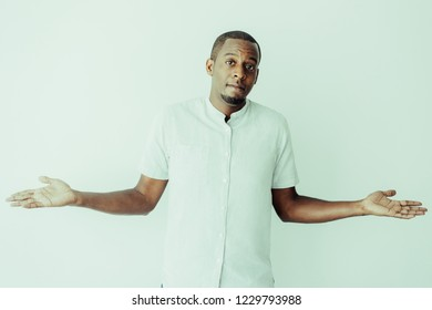 Puzzled African man with beard shrugging shoulders and looking at camera. Confused frowning handsome young African-American guy wearing casual shirt being in turmoil. Miscommunication concept