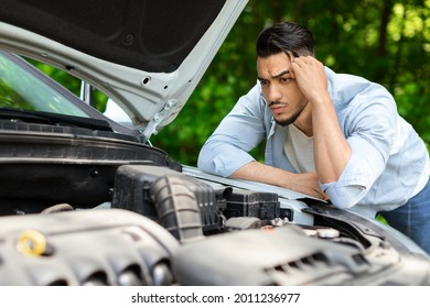 Puzzled arab man leaning on open car hood, looking at engine, having automobile crush in the middle of the road. Nervous middle-eastern guy driver waiting for car service, closeup photo