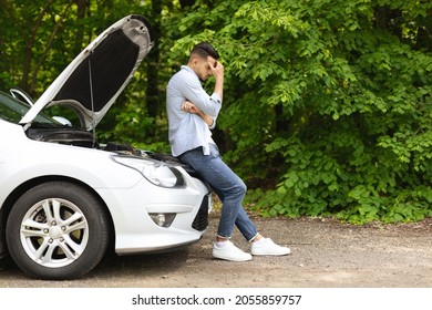 Puzzled arab man standing by open car hood, looking down, having automobile crush in the middle of the road. Nervous middle-eastern guy driver waiting for car service, panorama with copy space