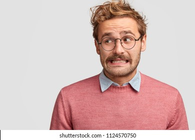 Puzzled attractive bearded emotive male wonk in spectacles, looks with worried embarrassed expression aside, being ignorant, poses against white studio background with blank free space on left