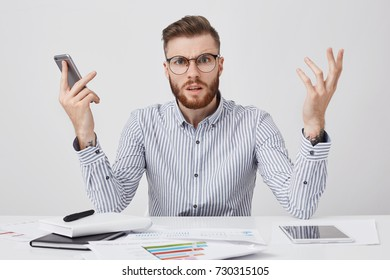 Puzzled bearded man with indignant look can`t understand why there is no answer from colleague, gestures in furious manner, keeps mobile phone in hand, surrounded with documents and tablet computer