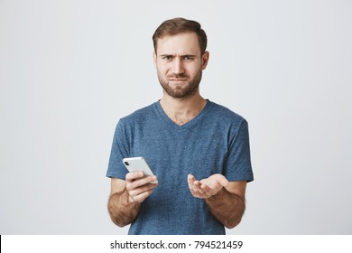 Puzzled bearded man looking with confusion at camera reading shocking news or browsing newsfeed via social networks using mobile phone, having small break. Face expression and reaction concept.