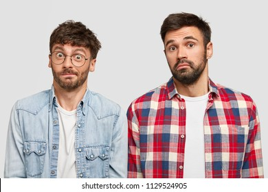 Puzzled bearded men with clueless expression, doesn`t know how make project work and from what to start, have puzzled looks, feel bewilderment, isolated over white background. So what to do?