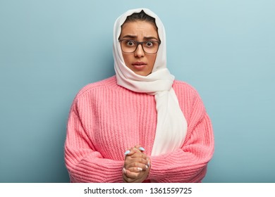 Puzzled beautiful woman of Islamic religion clasps hands together, has unexpected reaction, looks with great surprisement and scared expression, hears something bad, dressed in oversized jumper, scarf