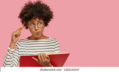 Puzzled black woman has contemplative expression, writes to do list of goals, holds notebook, scratches head with pencil, looks aside, being deep in thoughts, isolated on pink studio background