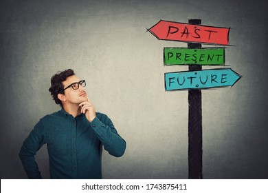 Puzzled businessman keeps hand under chin, thoughtful gesture, looking up at a signpost with arrows showing past, present and future directions. Business worker lost in time looking up focused.
