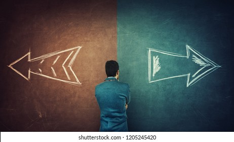 Puzzled businessman and a split blackboard with arrows going in two different ways red and blue side. Correct choice between left and right, failure or success. Difficult decision and doubt concept.