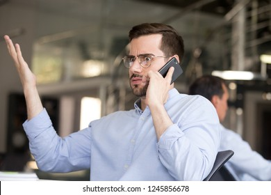 Puzzled businessman with wide eyes and raised hand talking on phone with partner in office at workplace receiving surprise news, unexpected result, manager having conversation with client or customer