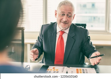 Puzzled ceo looking at infographics in doubts and talking to worker. Mid adult man in formal wear skeptically reviewing analytics or presentation in documents. Business meeting or negotiation concept
