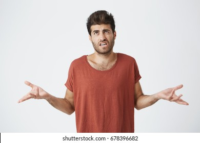 Puzzled and clueless bearded man with stylish hairstyle dressed in casual clothing shrugging shoulders and staring at camera with confused look after he made mistake but not feeling guilty for that.