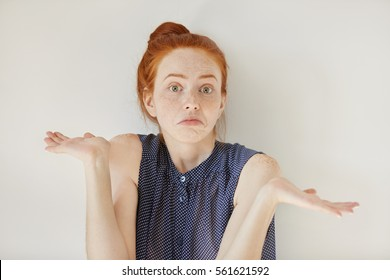 Puzzled and clueless young redhead woman with arms out, shrugging her shoulders, saying: who cares, so what, I don't know. Negative human emotions, facial expressions, life perception and attitude