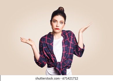 Puzzled and clueless young woman with arms out, shrugging her shoulders, saying: who cares, so what, I don't know. Negative human emotions, facial expressions, life perception and attitude.