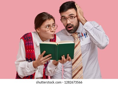Puzzled clumsy female and male readers look at textbook, have worried expressions, cram material, wear spectacles for good vision, isolated over pink background. Education and knowledge concept