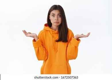 Puzzled and confused silly brunette girl looking for your help or advice, dont know what to do, shrugging with perplexed expression, being indecisive while facing tough decision, white background