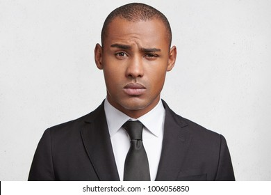 Puzzled dark skinned male enterpreneur, dressed formally, raises eyebrow in bewilderment, tries to make hard decision, poses against white background. People, business and occupation concept