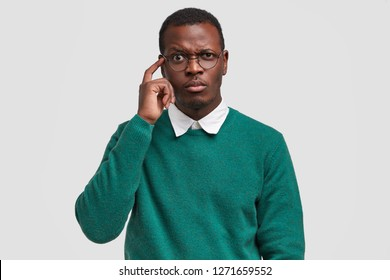 Puzzled dark skinned man frowns face, keeps index finger on temple, tries to concentrate, being deep in thoughts, wears green jumper, big spectacles, isolated over white background. Facial expressions