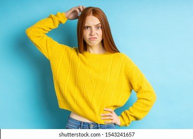 Puzzled displeased redhead lady scratching head, lifting eyebrow, trying to remember something, looking at camera with perplexed expression isolated over blue background..
