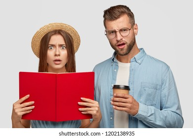 Puzzled, displeased students carry opened book, read information, prepare for final exam, enjoy hot aromatic beverage dressed in stylish clothes, isolated on white wall. Oh no why should we learn it?
