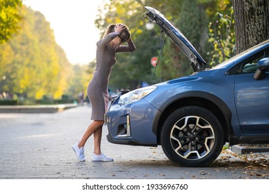 Puzzled female driver standing on a street near her car with popped up hood inspecting broken engine.
