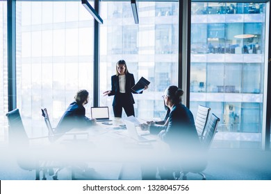 Puzzled female proud ceo carrying presentation with employees in conference room. Woman manager standing near meeting table while explaining strategy during meeting in office interior of skyscraper