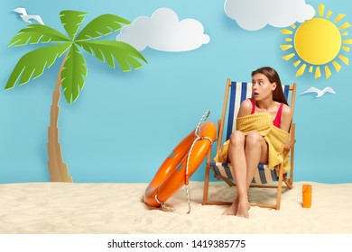 Puzzled female tourist wrapped in soft towel, focused aside with frightened expression, poses at deckchair has rest on sea feels cold recreats at paradise sandy beach. Holiday maker has summer holiday