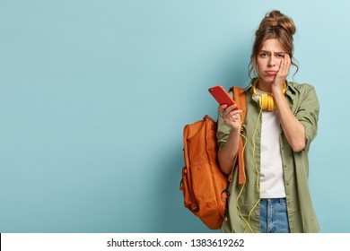 Puzzled gloomy young girl looks sadly at camera, cannot understand how to use new application, arent able to download song in playlist, has no internet connection, stands with rucksack over blue wall