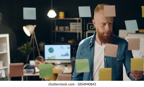Puzzled guy asking female colleague for advice in hipster office. Professional startup team working together on deadline indoors. Businesswoman consulting male coworker on problem at job