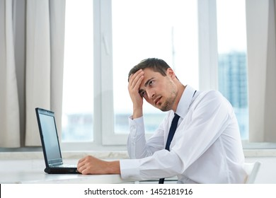 A puzzled man in a shirt sits at a table in front of a laptop and touches his head with his hand