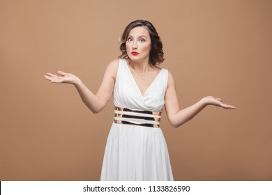 Puzzled middle aged woman say i don't know. Emotional expressing woman in white dress, makeup, red lips and dark curly hairstyle. Studio shot, indoor, isolated on beige or light brown background