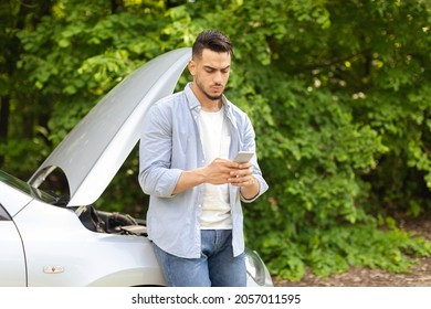 Puzzled middle-eastern guy driver standing by broken car, using cellphone, watching videos on Internet, trying to fix automobile, young arab man looking for auto service, copy space