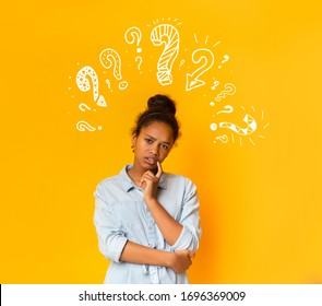Puzzled pensive young african american teen girl in casual t-shirt posing over orange background with white question marks