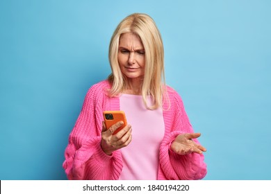 Puzzled retired woman uses mobile phone looks confused smirks face as cannot download new application dressed in casual jumper isolated on blue background. Modern technologies and people concept