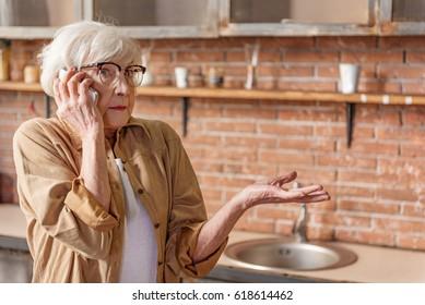 Puzzled senior lady talking on mobile phone
