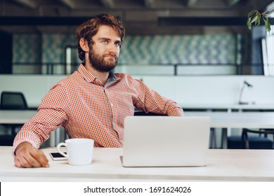 Puzzled thoughtful businessman sitting at his working table in an office. Business concept