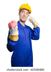 Puzzled workman holding a brain on white background