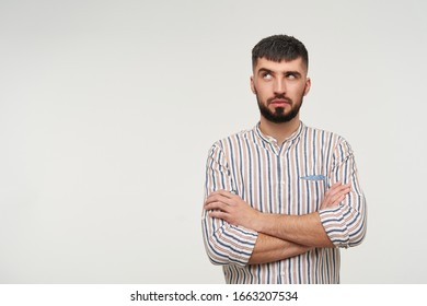 Puzzled young pretty brunette bearded man raising his eyebrow while looking pensively upwards and folding hands on his chest, isolated over white background