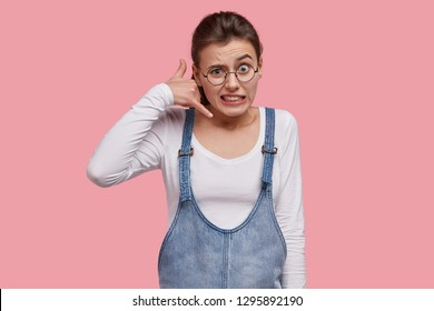 Puzzled young woman clenches teeth, makes phone gesture, wears casual clothes, raises eyebrows in bewilderment, has round spectacles, stands against pink background, pretends calling someone.