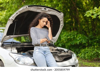 Puzzled young woman driver leaning on open car hood, having automobile crush in the middle of the road. Nervous middle-eastern lady waiting for car service, closeup photo, copy space