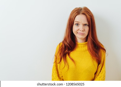 Puzzled young woman pulling a whimsical expression raising an eyebrow at the camera against a white wall with copy space