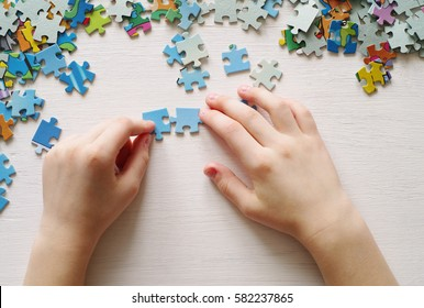 Puzzles. Baby hand fold puzzle, closeup, top view