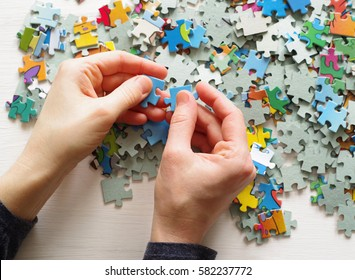 Puzzles. Female hands folded puzzles, closeup, top view