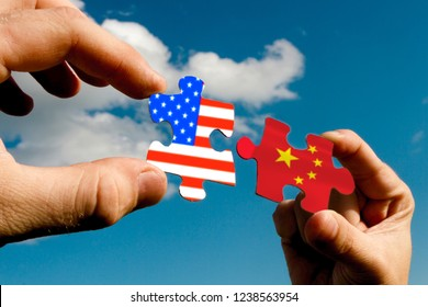 puzzles in the form of flags of China and USA of America in the hands of people against the sky. Agreement, peace, friendship. The solution to the trade war