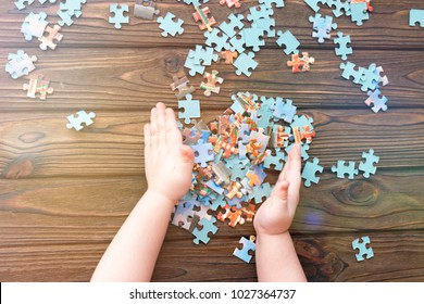 puzzles, hands on the background of a wooden table. logical game.