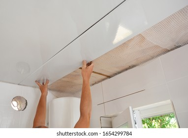 PVC Ceiling Panels, Cladding Installation. Builder installing, renovate, repair white PVC Ceiling Boards in the bathroom