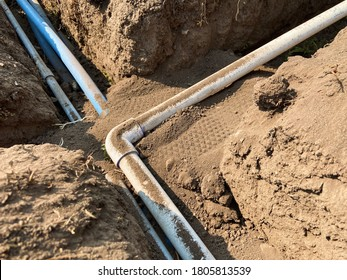 PVC pipe, blue pipe, and electrical conduit running through trench filled with dirt