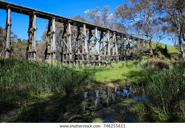 PYALONG, CENTRAL VICTORIA, AUSTRALIA : 23 OCTOBER 2017 - Historic wooden railway trestle bridge near Pyalong in Central Victoria, partially reflected in small creek.