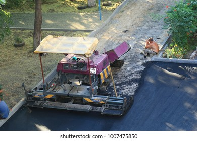 Pyatigorsk, Russia - August 10, 2017: Workers are resting near the asphalt paver in the evening. Works by laying asphalt on a narrow street in Pyatigorsk