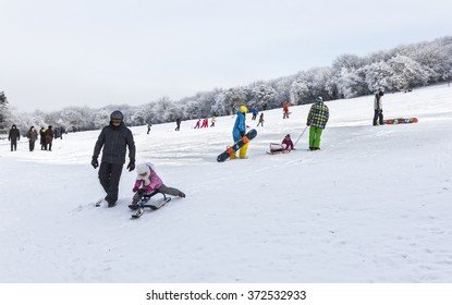 Pyatigorsk, Russia - January 02, 2016: Adults and children sledding and snowboarding on the slope of the mountains in winter sunny day.