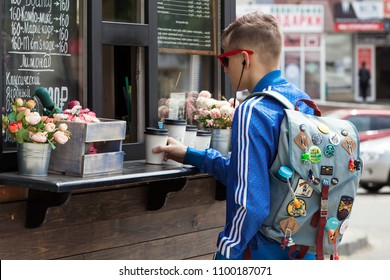 Pyatigorsk, Russia, May 27, 2018: A young man in red glasses and with a backpack on his shoulders buys coffee in a street coffee shop
